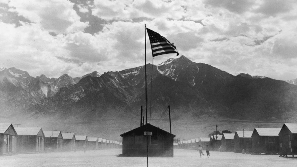 A U.S. flag flies at a Japanese-American internment camp, which is surrounded by mountains in Manzanar, California, 1942. (Credit: Hulton Archive/Getty Images)