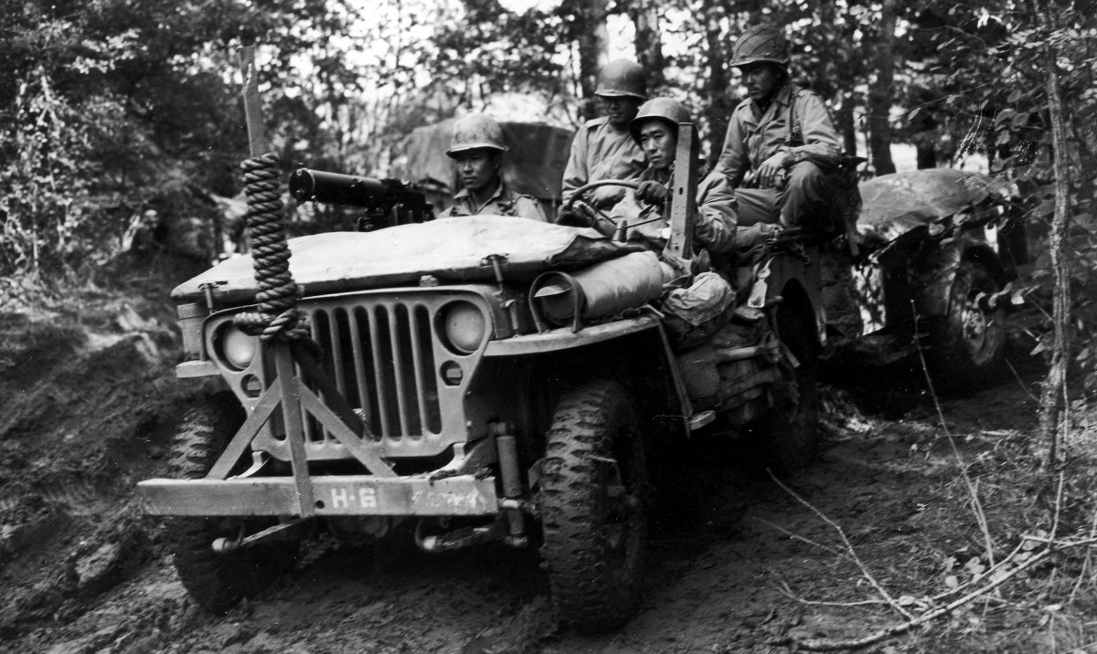 Four Japanese-American servicemen riding in a jeep, towing a supply trailer on a rural road in France during World War II. (Credit: Hulton Archive/Getty Images)