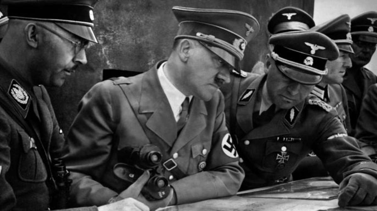 German Nazi Chancellor and dictator Adolf Hitler consulting a geographical survey map with his general staff including Heinrich Himmler and Martin Bormann duringWorld War II, 1939. (Credit: France Presse Voir/AFP/Getty Images)