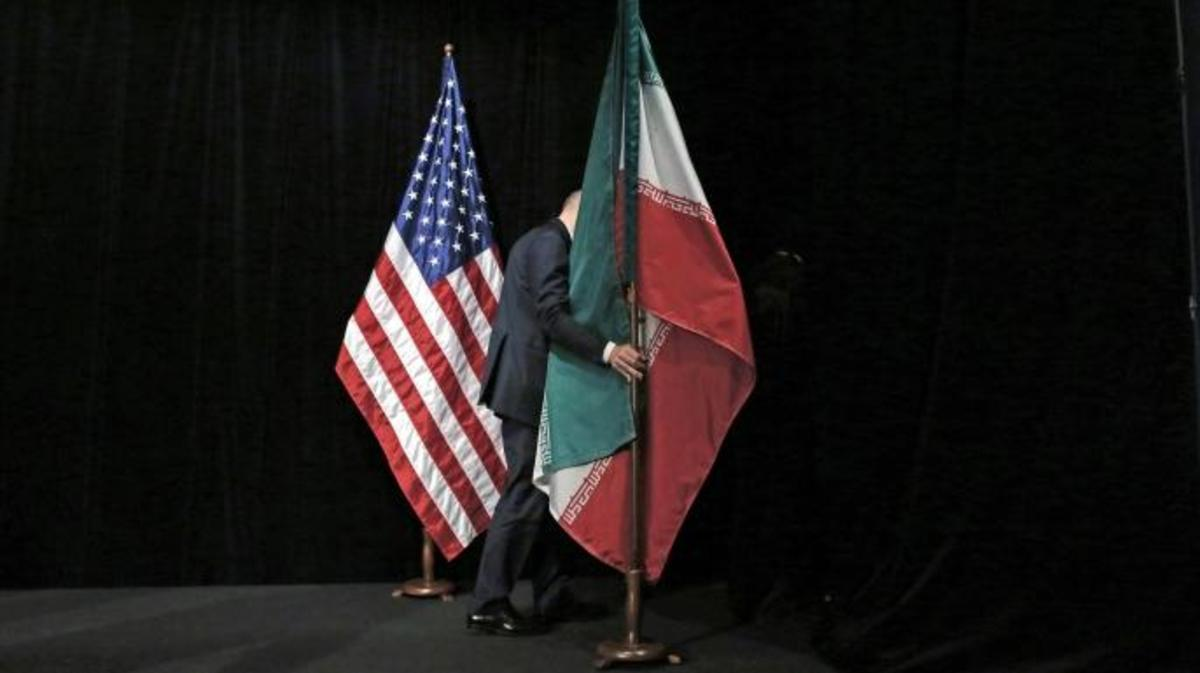 The Iranian and U.S. flag on stage, after a group picture with foreign ministers and representatives of US, Iran, China, Russia, Britain, Germany, France and the EU during the Iran nuclear talks at the Vienna International Center in Vienna on July 14, 2015. (Credit: CARLOS BARRIA/AFP/Getty Images)