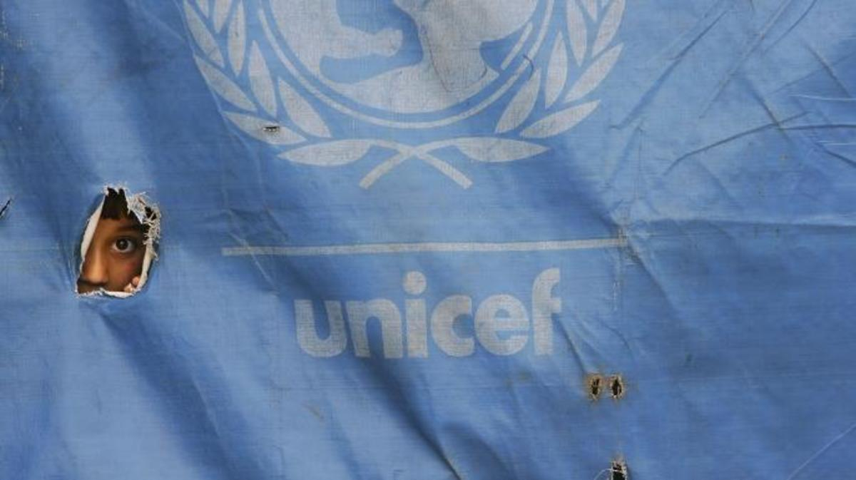 A girl peeks out from a UNICEF school tent in Faisabad.  (Credit: Paula Bronstein/Getty Images)