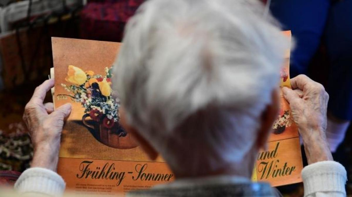 A resident looks at a magazine inside an east German 60s lounge at a nursing home in Dresden, Germany. (Credit: Tobias Schwarz/AFP/Getty Images)