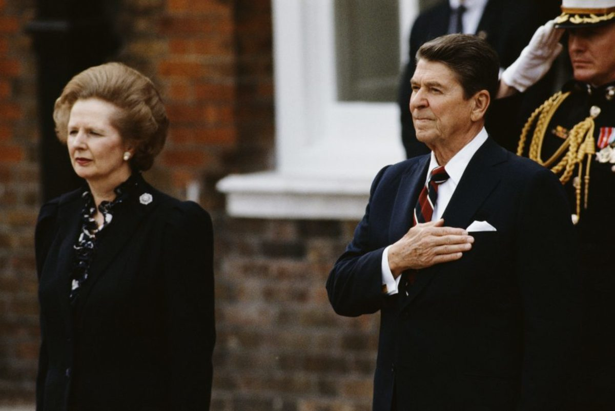 British Prime Minister Margaret Thatcher (center, left) stands with U.S. President Ronald Reagan (center), as they listen to the American national anthem at Kensington Palace Gardens after Reagan's arrival in June 1984. (Photo by Bryn Colton/Getty Images)