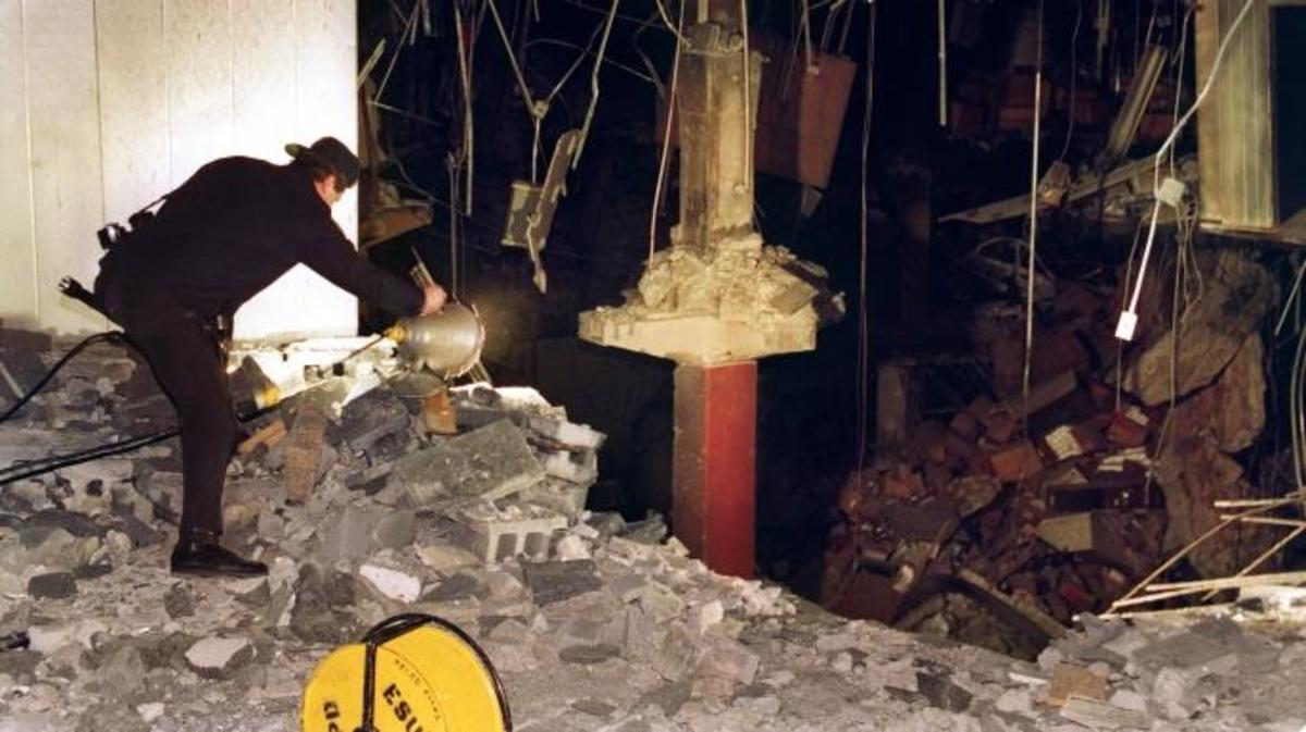 A police photographer examines damage to an underground paring garage following the 1993 World Trade Center bombing.