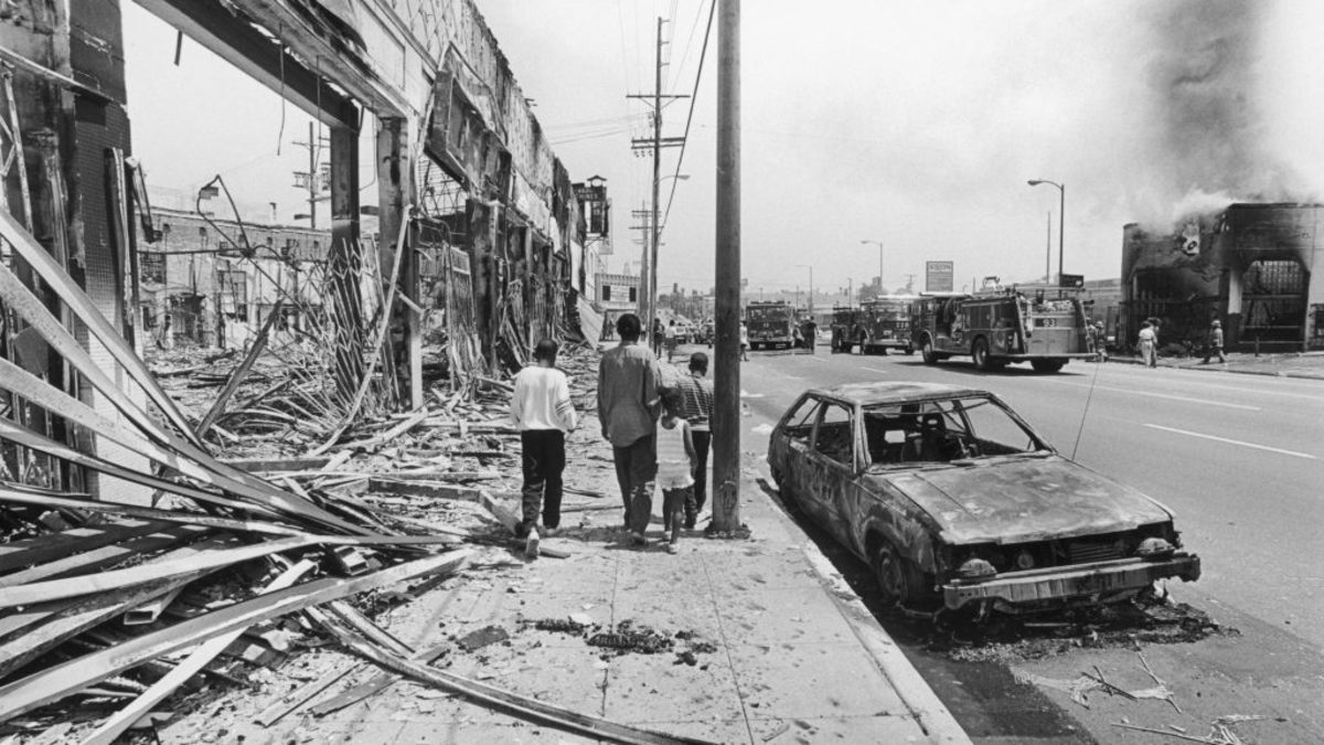 Residents of South Central Los Angeles walk through a neighborhood burned down during the 1992 riots that swept the area after police officers accused of beating motorist Rodney King were cleared of all charges.  (Photo by Ted Soqui/Corbis via Getty Images)