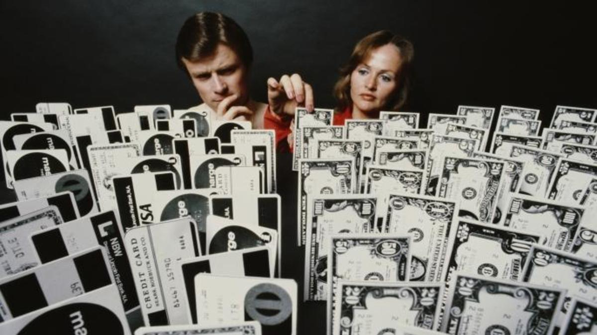 A man and a woman overlooking an array of credit cards and money, 1979. (Credit: Alfred Gescheidt/Getty Images)