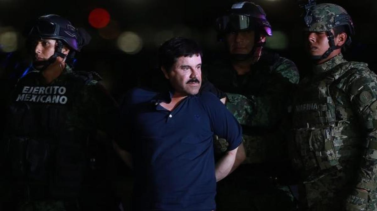 "Joaquin ""El Chapo"" Guzman, the world's most wanted-drug trafficker, center, is escorted by Mexican security forces at a Navy hangar in Mexico City, Mexico, on Friday, Jan. 8, 2016. (Credit: Susana Gonzalez/Bloomberg via Getty Images)"