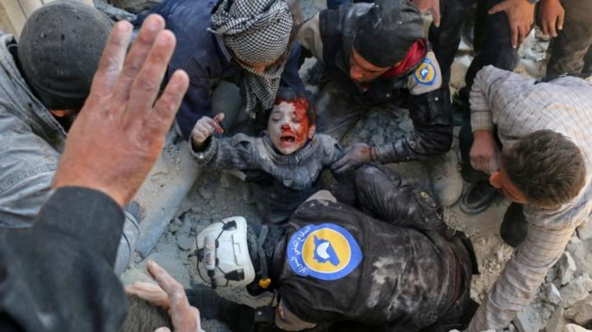 The White Helmets rescue a boy from the rubble following a reported barrel bomb attack on the Bab al-Nairab neighborhood of the northern Syrian city of Aleppo on November 24, 2016. (Credit: AMEER ALHALBI/AFP/Getty Images)