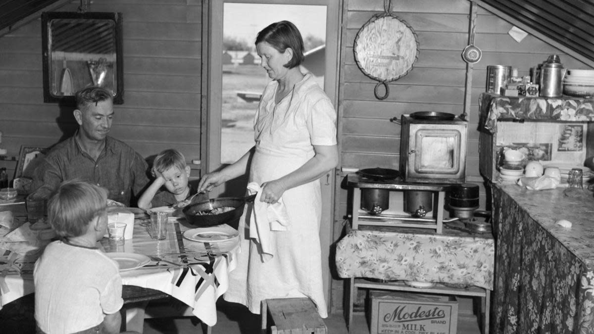 A mother serving dinner in the clean surroundings of a Farm Security Administration camp in Visalia, California, 1939. (Credit: Bettmann Archive/Getty Images)