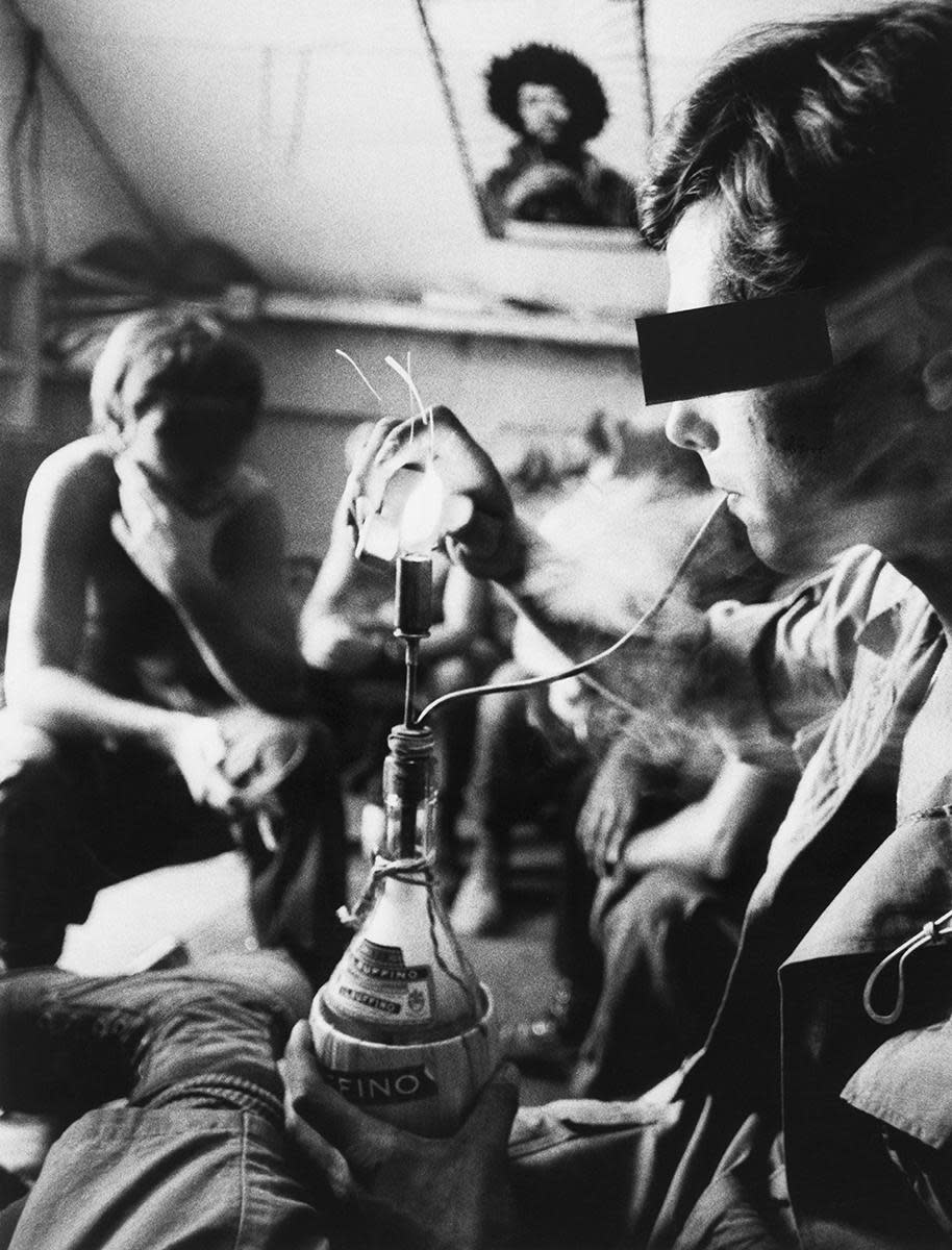 GIs lighting up a homemade hookah, made from a wine bottle and a .45 caliber shell. (Credit: Bettmann Archive/Getty Images)