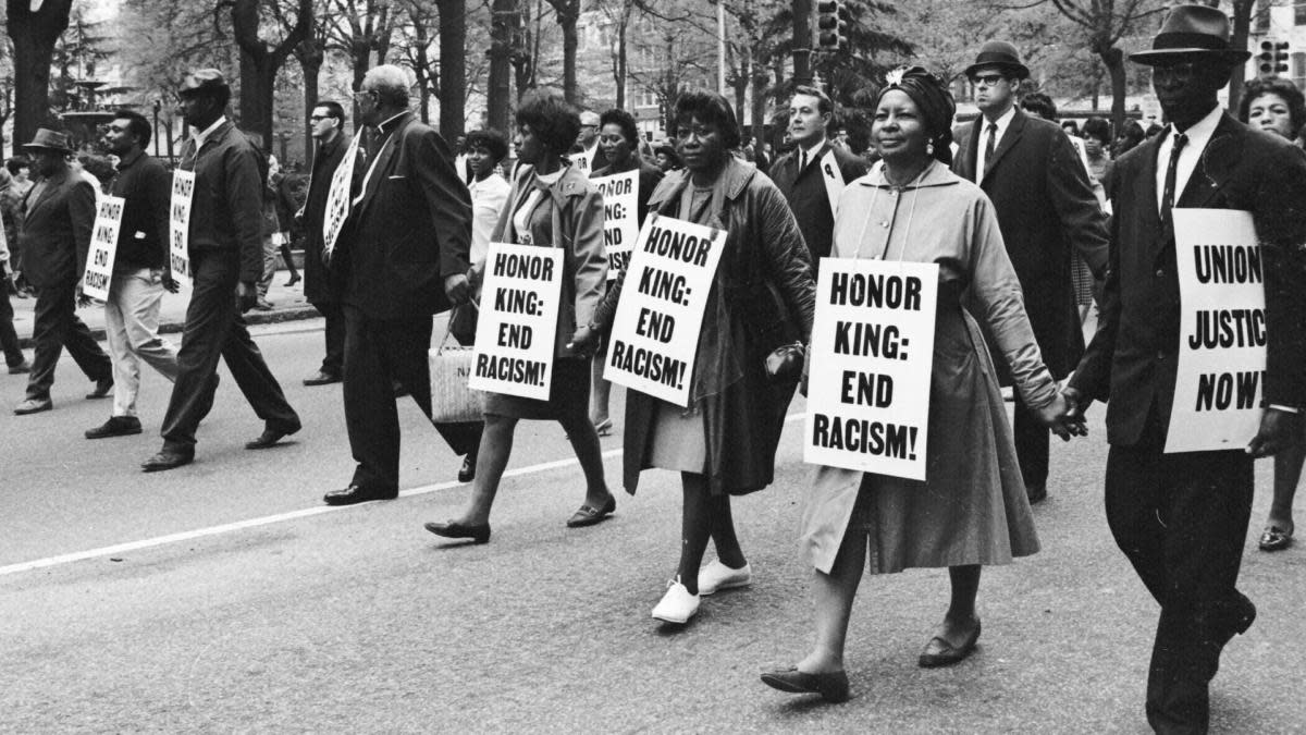 Marchers wearing signs that read 'Honor King: End Racism!' and 'Union Justice Now' as they participate in the Sanitation Workers march, soon after the assassination of Dr. Martin Luther King, Jr. (Credit: Robert Abbott Sengstacke/Getty Images)