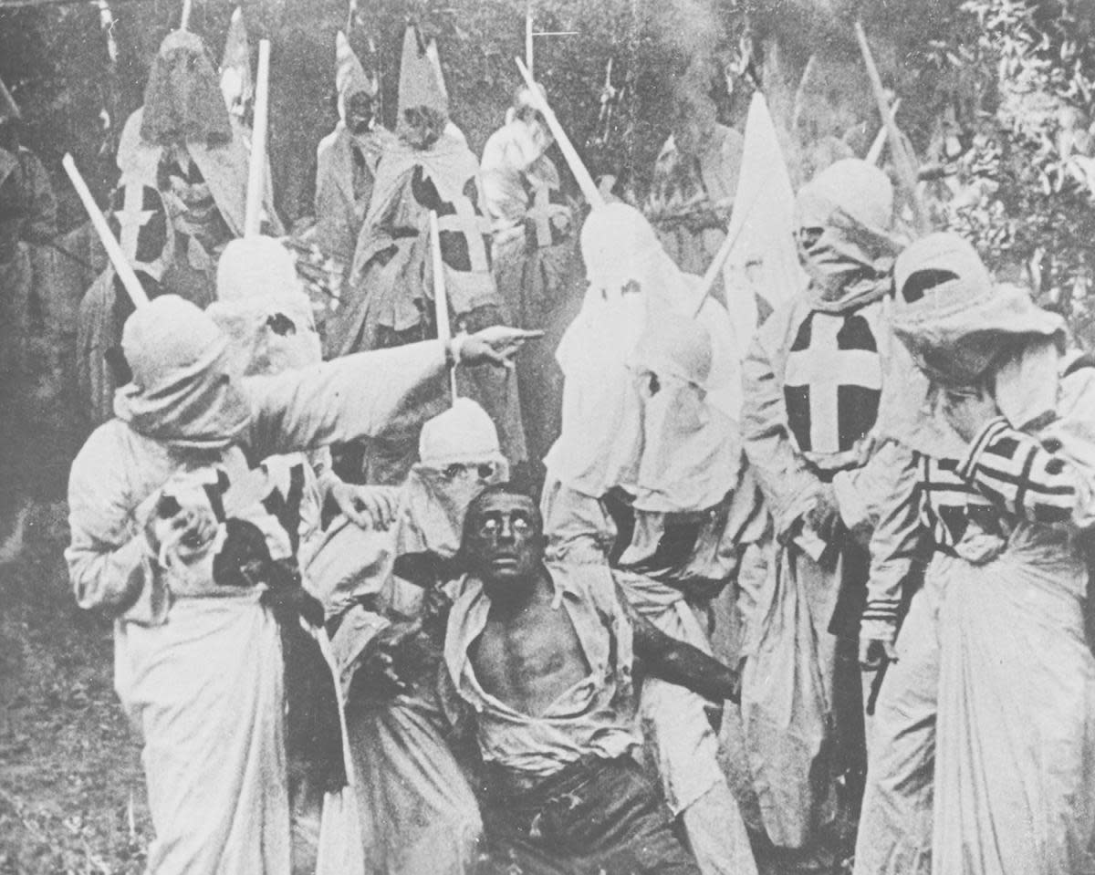 "Black and white photograph of a group of Klansmen surrounding freedman Gus (played by white actor Walter Long in blackface) in a scene from director D W Griffith's motion picture ""The Birth of a Nation"", 1915. (Credit: New York Public Library/Smith Collection/Gado/Getty Images)"
