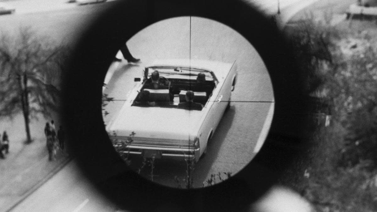A view through a gun sight from the Texas School Book Depository is part of a reenactment of the Kennedy assassination. This evidence was submitted to the Warren Commission. (Credit: Corbis via Getty Images)