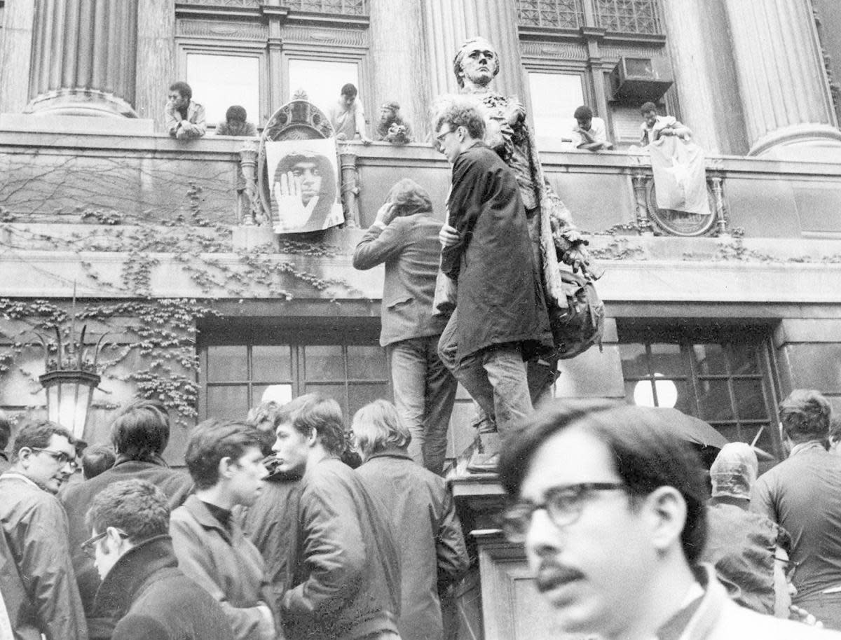 Students protesting the construction of the gymnasium in Morningside Park and the University's participation in a defense-related program outside of Hamilton Hall. A couple of students stand on pedestal of the statue of Alexander Hamilton while others hang a poster of Stokely Carmichael from the balcony of the building along with a Viet Cong flag. (Credit: Jacob Harris/AP Photo)