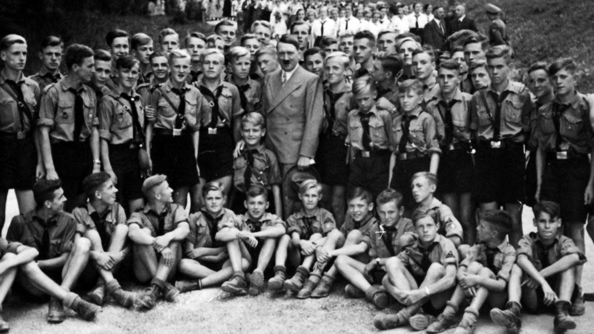 Adolf Hitler with Nazi party Hitler Youth at a 1935 gathering. (Credit: Universal History Archive/UIG via Getty Images)