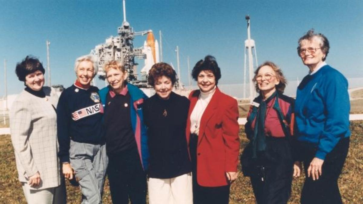 "Members of the First Lady Astronaut Trainees (FLATs), also known as the ""Mercury 13"" (from left) Gene Nora Jessen, Wally Funk, Jerrie Cobb, Jerri Truhill, Sarah Rutley, Myrtle Cagle and Bernice Steadman. These seven women who once aspired to fly into space stand outside Launch Pad 39B near the Space Shuttle Discovery in this photograph from 1995. (Credit: NASA)"