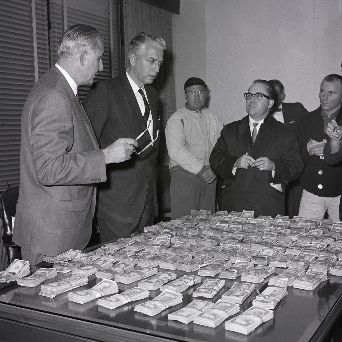 Chief FBI agent William G. Simons of Los Angeles and FBI Assistant Director Joseph Casper show newsmen the money recovered with the capture of three men in connection with the Frank Sinatra, Jr. kidnapping. (Credit: Bettmann Archive/Getty Images)
