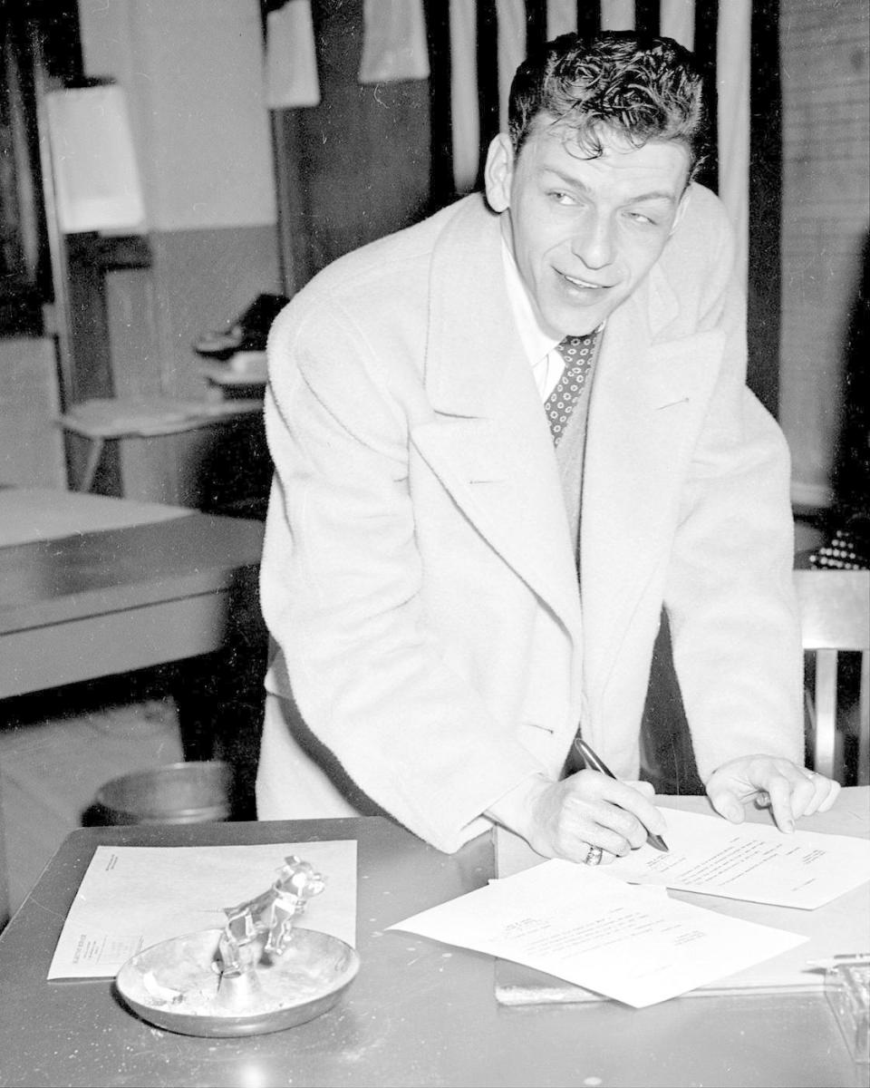 "Frank Sinatra signing papers before leaving his draft board in Newark, New Jersey. Speaking of his rejection, the singer said, ""I am very unhappy about it. If I had been accepted, I would have preferred the Army or Marines."" (Credit: NY Daily News Archive/Getty Images)"