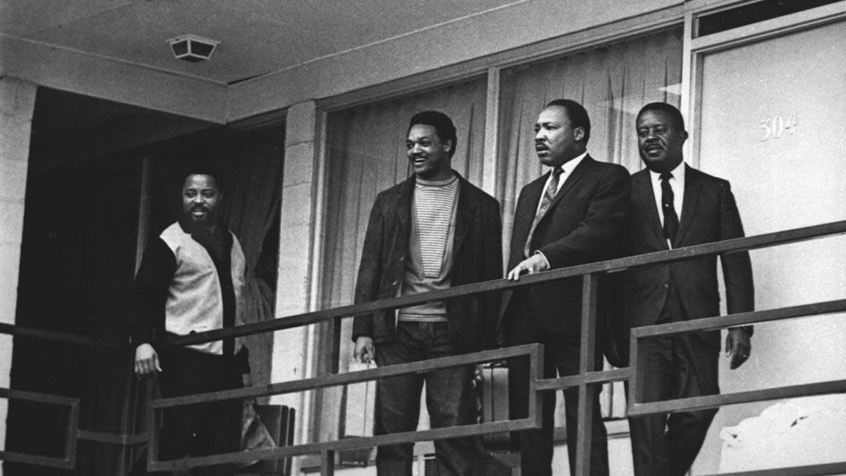 Martin Luther King, Jr. standing  with Hosea Williams, Jesse Jackson and Ralph Abernathy on April 3, 1968, on the Lorraine Motel balcony approximately in the same spot where he would be assassinated the following day. (Credit: Charles Kelly/AP Photo)