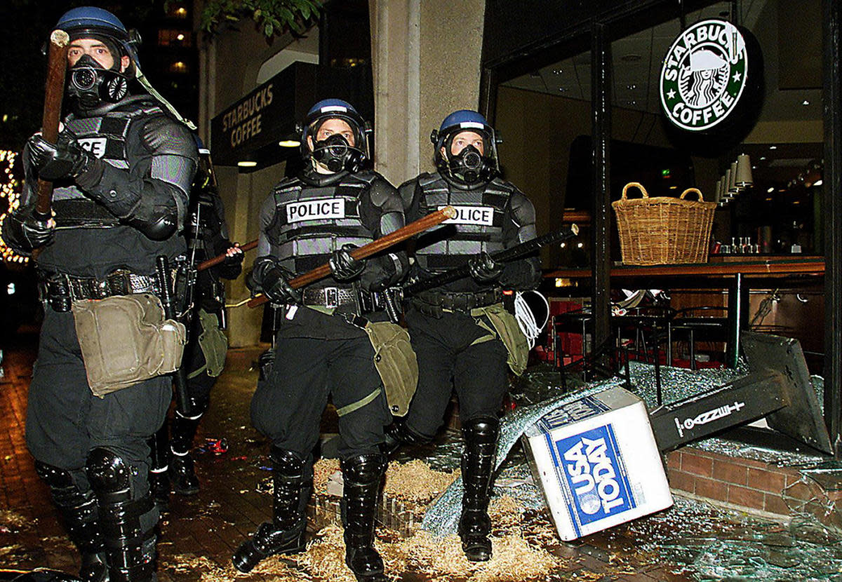 Seattle riot police marching past a damaged Starbucks during demonstrations against the World Trade Organization, 1999.