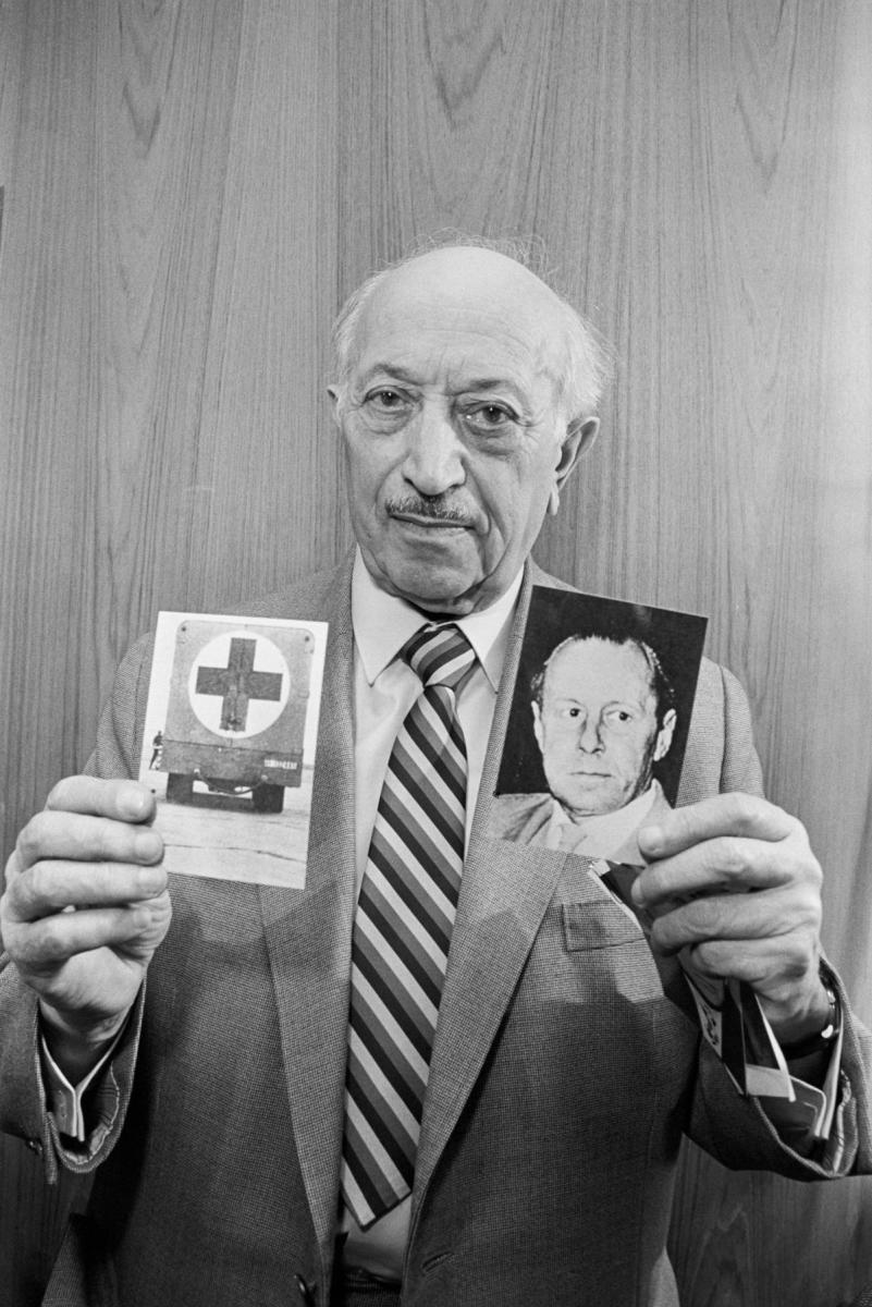 Nazi hunter Simon Wiesenthal holding photographs depicting former Gestapo chief Walter Rauff and a mobile gas-chamber van he created to execute Jews. Rauff was protected from prosecution by Chilean president Augusto Pinochet. (Credit: Bettmann Archive/Getty Images)