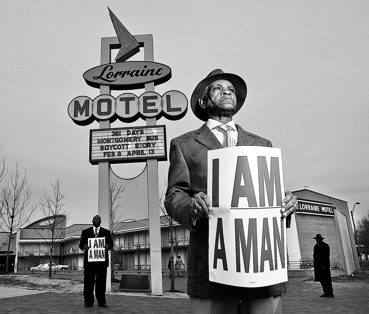 Memphis sanitation workers Elmore Nickelberry, 76, center, and his son, Terrence, left, holding replica signs used by the 1968 Memphis strikers, in front of the former Lorraine Motel where Martin Luther King, Jr. was assassinated, 2008. (Credit: Carl Juste/Miami Herald/MCT via Getty Images)