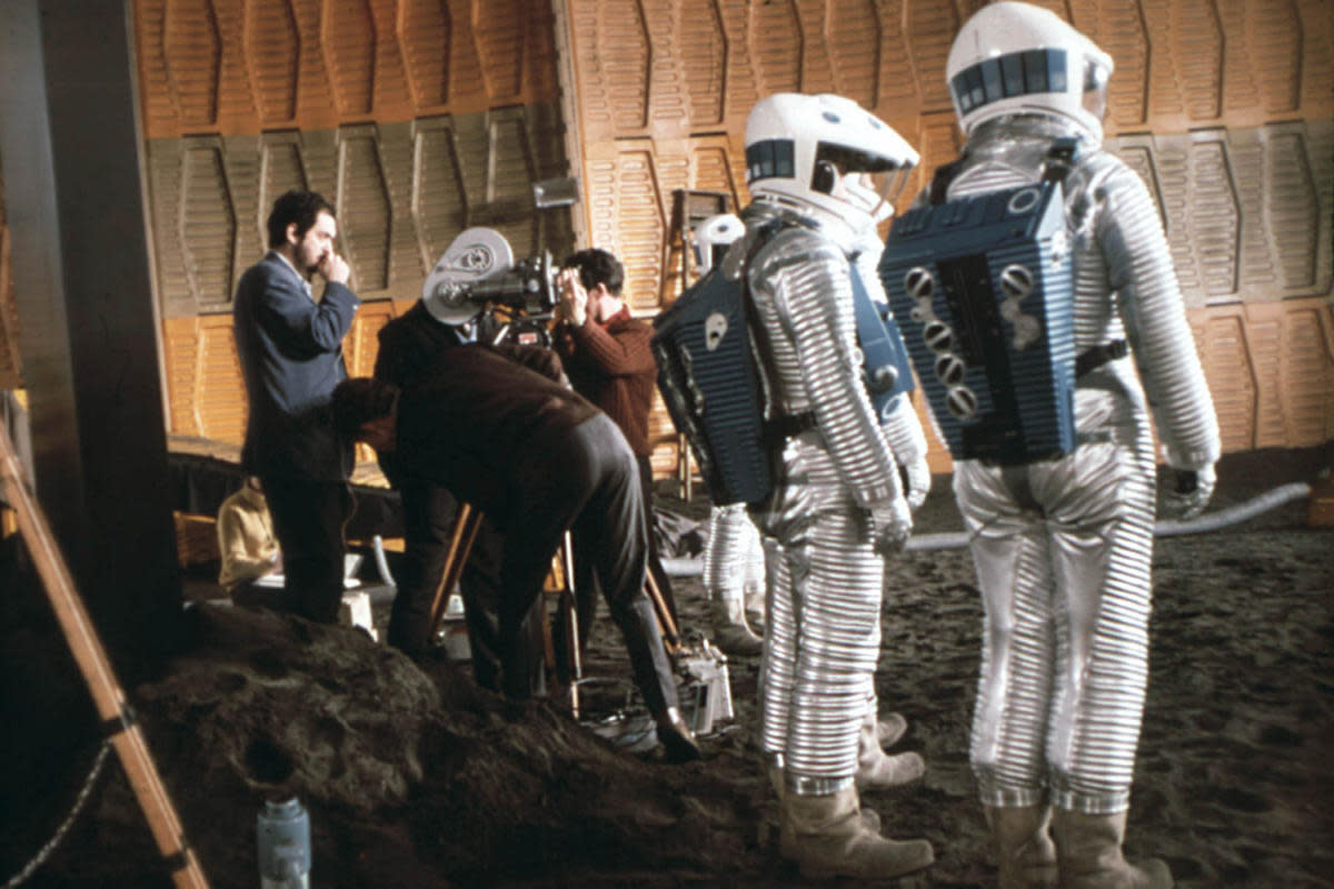 Director Stanley Kubrick on set. Before the days of digital effects, he had 90 tons of sand dyed dark gray to simulate the surface of the moon. (Credit: Mary Evans/MGM/Polaris/Stanley Kubrick Productions/Ronald Grant/Everett)