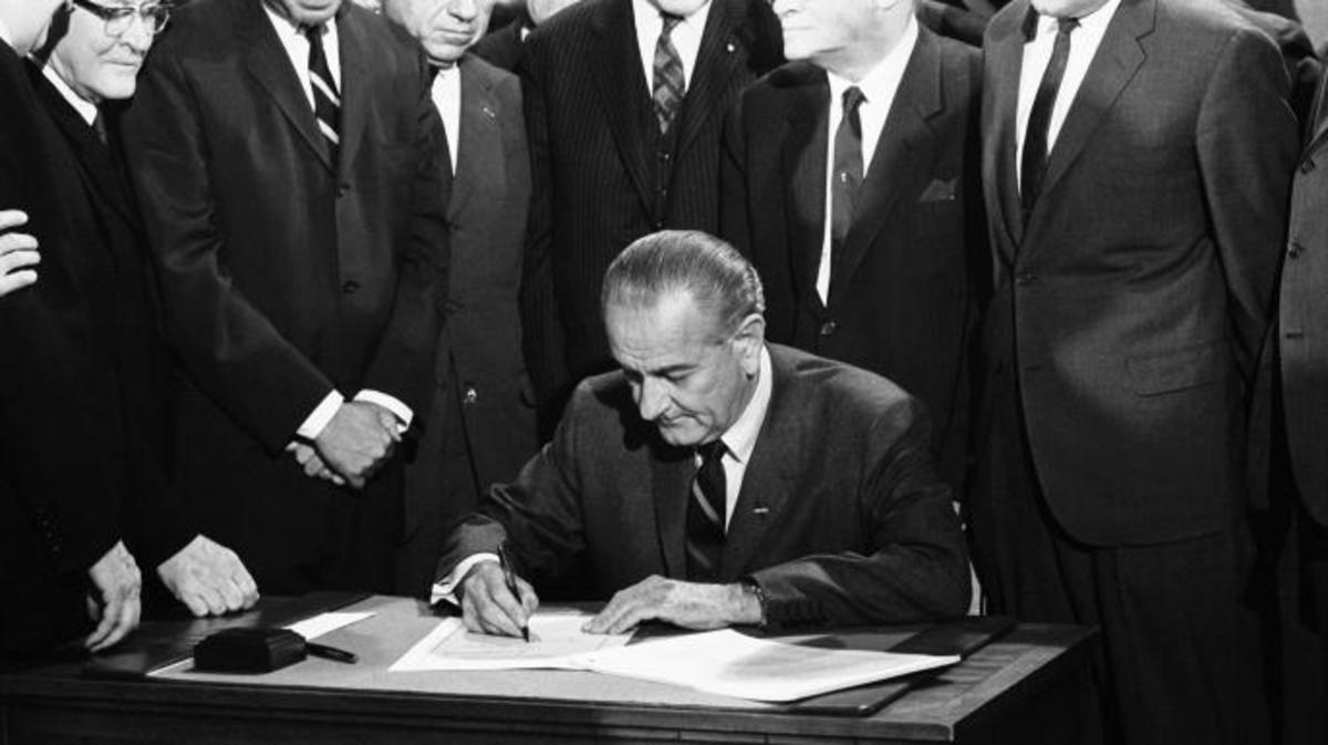 President Lyndon Johnson signs the Civil Rights bill while seated at a table surrounded by members of Congress. (Credit: Warren Leffler/Underwood Archives/Getty Images)
