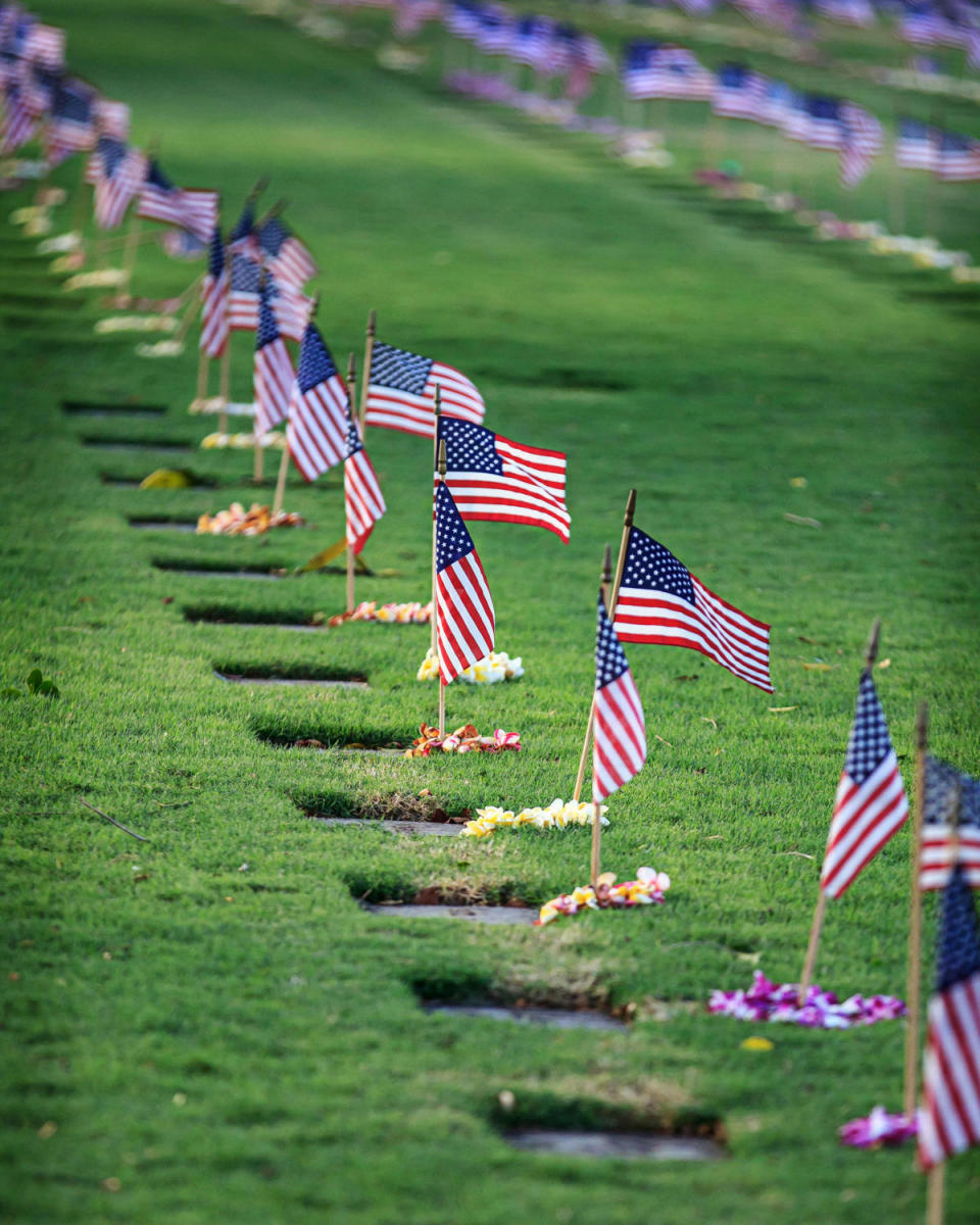 United States flags and flower lei adorn grave sites at the National Cemetery of the Pacific, the Punchbowl Cemetery, in Honolulu, Hawaii, 2013. (Credit: Julie Thurston Photography/Getty Images)