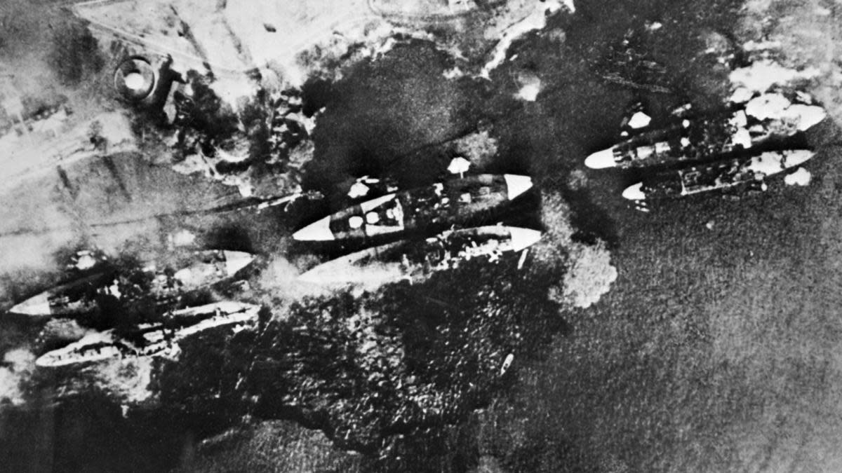 An aerial view of battleships of the US Pacific Fleet consumed by the flames in its home base at Pearl Harbor after a massive surprise attack. (Credit: HO/AFP/Getty Images)