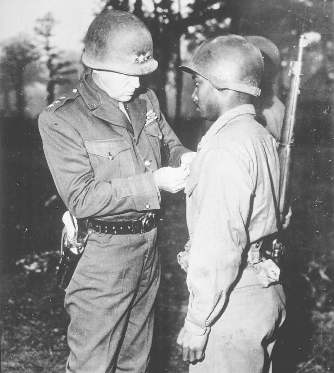 General George S. Patton, U.S. Third Army commander, pinning the Silver Star on Private Ernest A. Jenkins of New York City for his conspicuous gallantry in the liberation of Chateaudun, France, 1944. (Credit: The National Archives)
