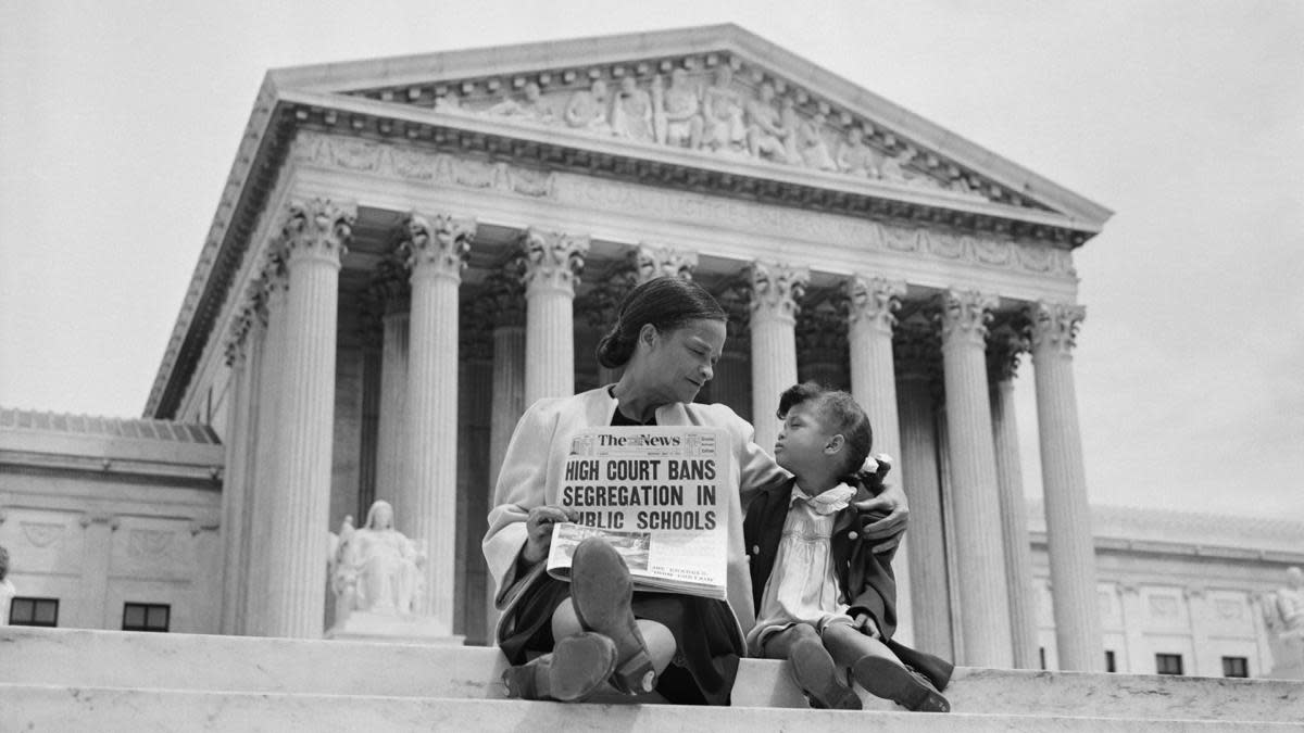 Nettie Hunt explaining to her daughter Nickie the meaning of the high court's ruling in the Brown v. Board of Education case on the steps of the U.S. Supreme Court. (Credit: Bettmann Archive/Getty Images)