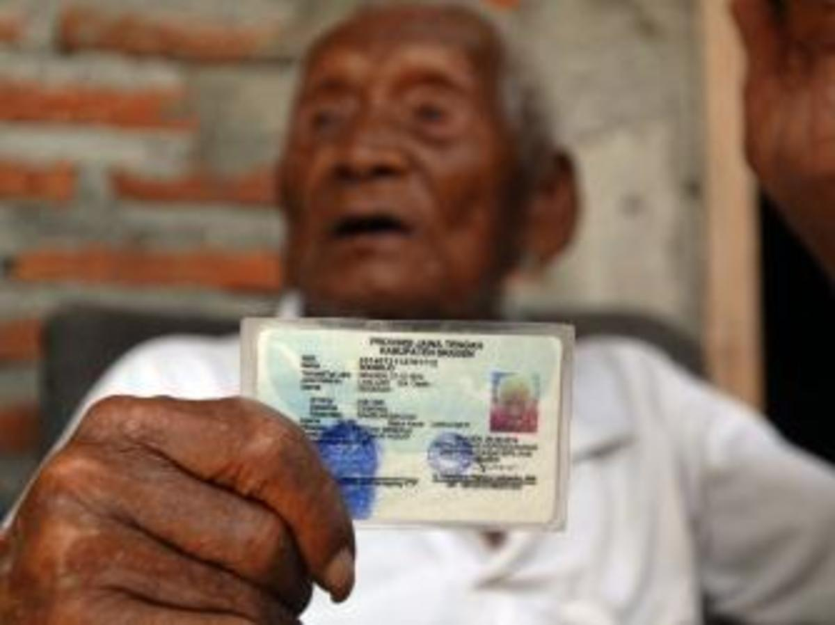 An Indonesian man, named Mbah Gotho, claimed to be 146 years old, is the oldest human in world's history shows his identity card to press members at his family house in Sragen, Central Java, Indonesia. (Credit: Anadolu Agency / Getty Images)      (Photo by Dasril Roszandi/Anadolu Agency/Getty Images)