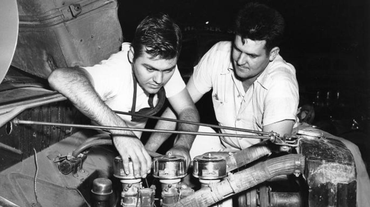 Junior Johnson (left) helping tune a souped-up engine that was used in cars that delivered moonshine in the rural Southern U.S.  Johnson grew up on a farm and, like many of the pioneers of stock car racing, developed his driving skills running moonshine as a young man. (Credit: ISC Images & Archives via Getty Images)