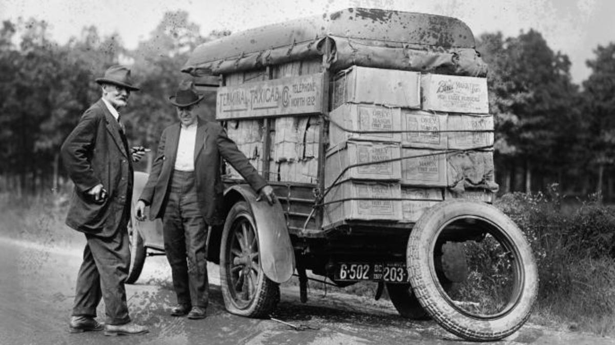 Agents capture a vehicle marked as a taxi loaded with liquor piled high as it got a flat tire, 1922. (Credit: Buyenlarge/Getty Images)
