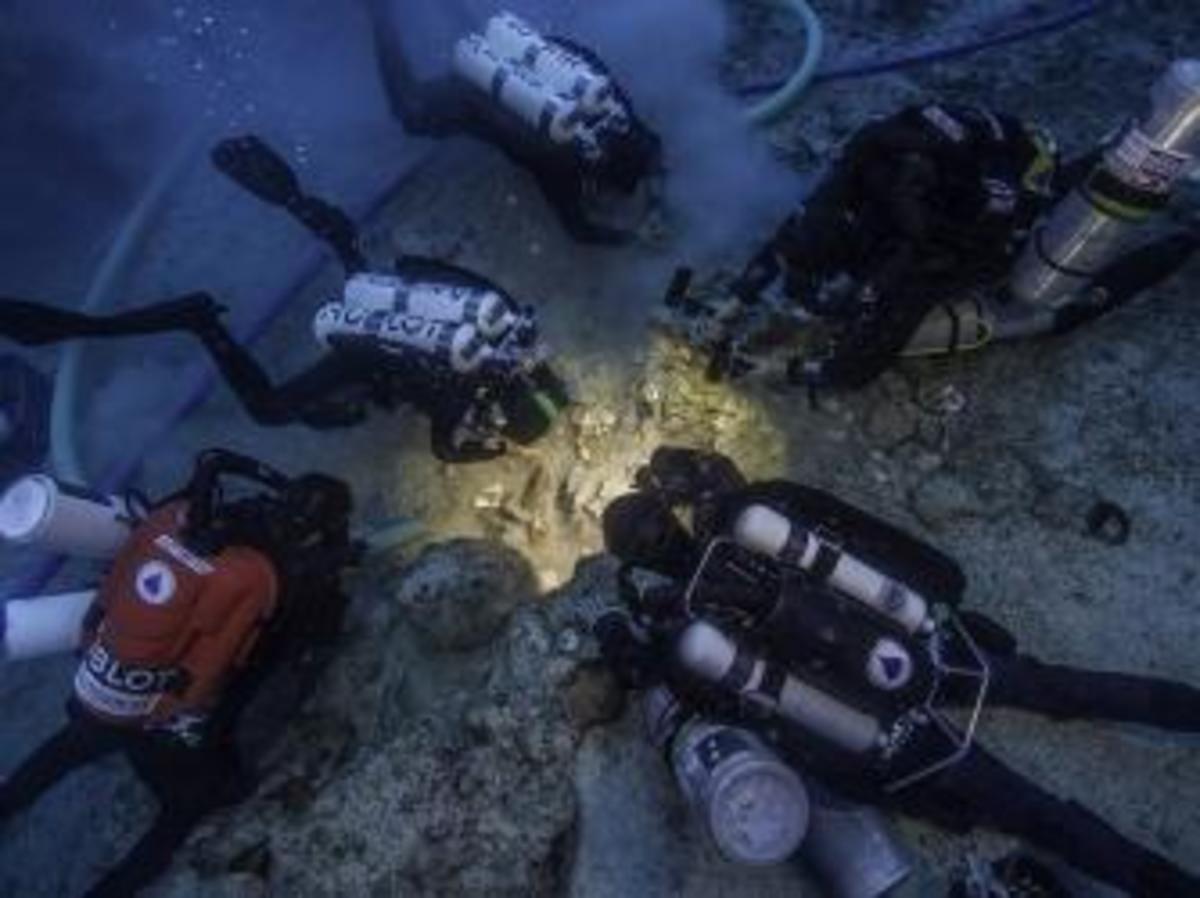 Archaeologists Brendan Foley, Theotokis Theodoulou and Alex Tourtas excavate the Antikythera Shipwreck skeletal remains, assisted by Nikolas Giannoulakis and Gemma Smith. (Credit: Brett Seymour / EUA/WHOI/ARGO)