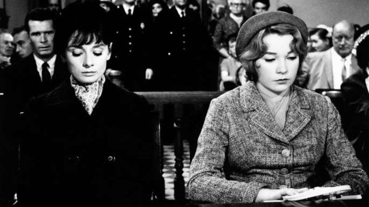 "Audrey Hepburn and American actress Shirley MacLaine sitting together in a courtroom in film version of ""The Children's Hour."" (Credit: Mondadori Portfolio/Getty Images)"
