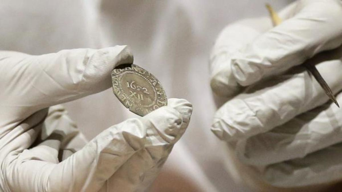 "Hatchfield holding the 1652 ""Pine Tree Shilling"" found in the capsule"