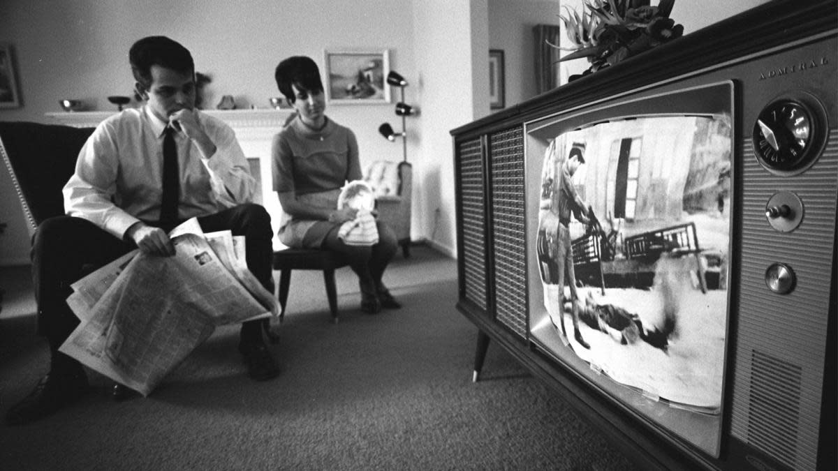 A couple watching news footage of the Vietnam war in their home. (Credit: Photo 12/UIG/Getty Images)