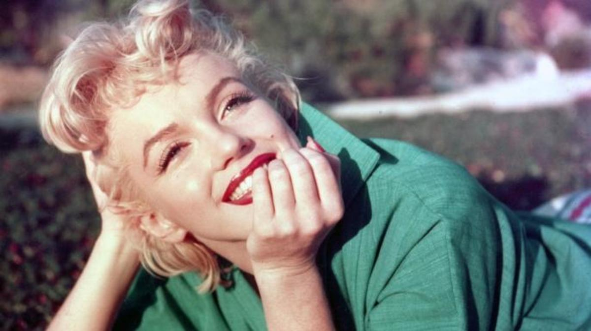 Actress Marilyn Monroe poses for a portrait laying on the grass in 1954 in Palm Springs, California. (Photo by Baron/Getty Images)