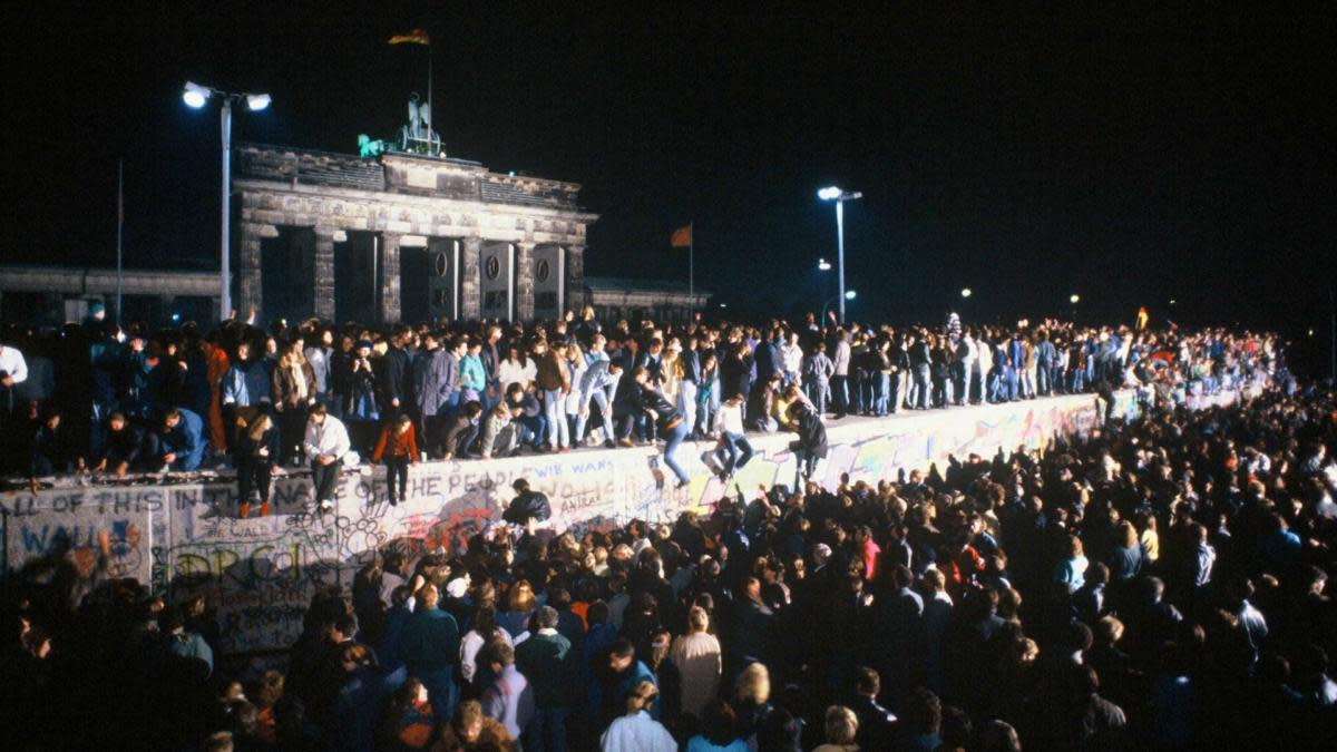 Thousands of celebrants climb atop the Berlin Wall in front of Brandenburg Gate on the night of November 9th, 1989. Crowds had flocked to the border crossings after a botched news announcement spread rapidly that the East German Government would start granting exit visas to anyone who wanted to go to the West. (Credit: Robert Wallis/Corbis via Getty Images)