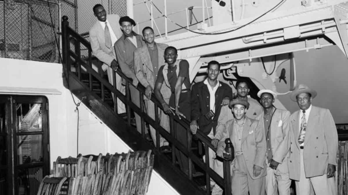 """Members of the Globetrotters basketball team are shown arriving in New York aboard the liner Mauretania. From top to bottom are: Louis Pressly; William """"Rookie"""" Brown; Boyd Buie; Reece """"Goose"""" Tatum; Frank Washington; Markus Haynes; Sammy Quee; Clarence Wilson; and (in front) manager Winfield Welch. (Credit: Bettmann / Contributor)"""