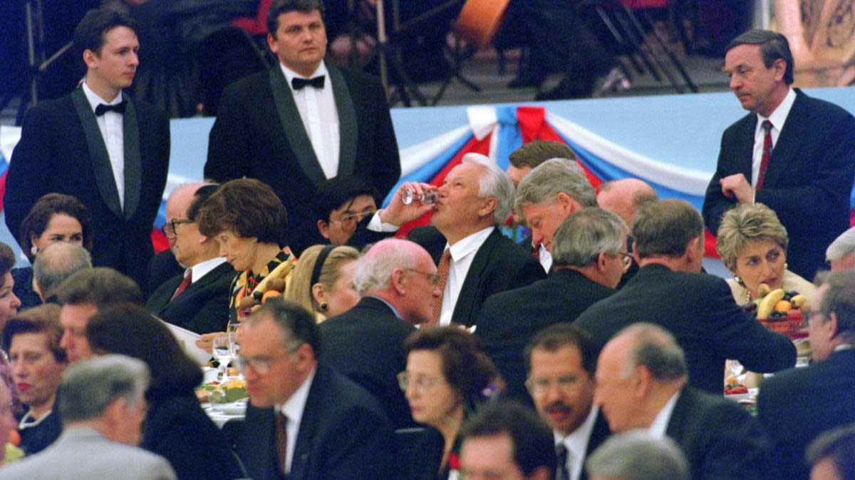 Russian President Boris Yeltsin finishing his glass of vodka next to President Bill Clinton in 1995 as Russia celebrated the 50th anniversary of the end of World War II in Europe. (Credit: Gerard Fouet/AFP/Getty Images)