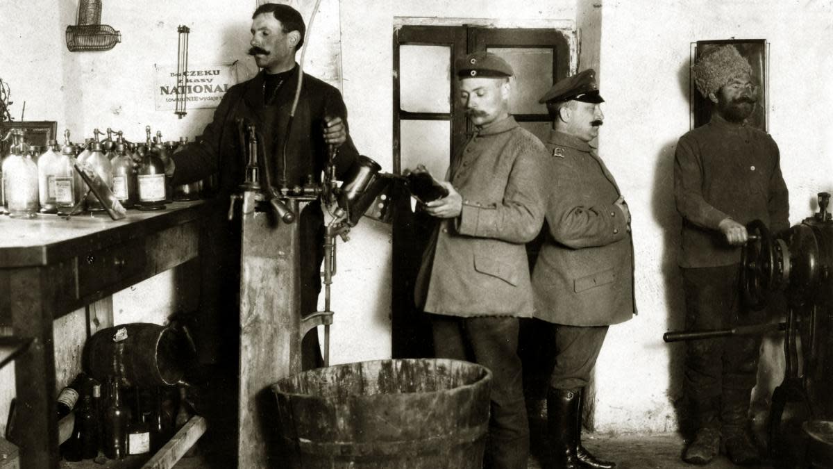 A German regimental chemist with his assistants making poison gas in a makeshift laboratory during the occupation of Poland during World War One. On the right is a Russian prisoner set to work by the Germans. (Credit: Popperfoto/Getty Images)