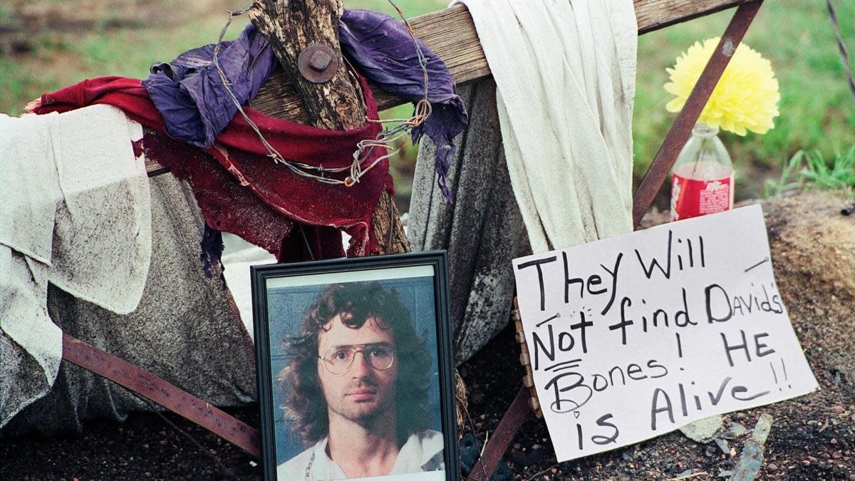 A photo of David Koresh resting beside a wooden cross as part of a monument erected in Waco, Texas by supporters of the Branch Davidian leader and founder. (Credit: NewsBase/AP Photo)