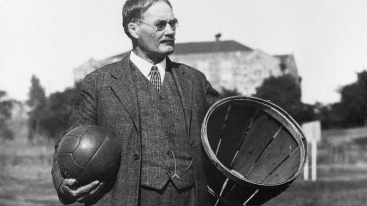 The inventor of basketball, Dr. James Naismith, stands in a field carrying a ball and a basket. (Credit: Bettmann/Getty Images)