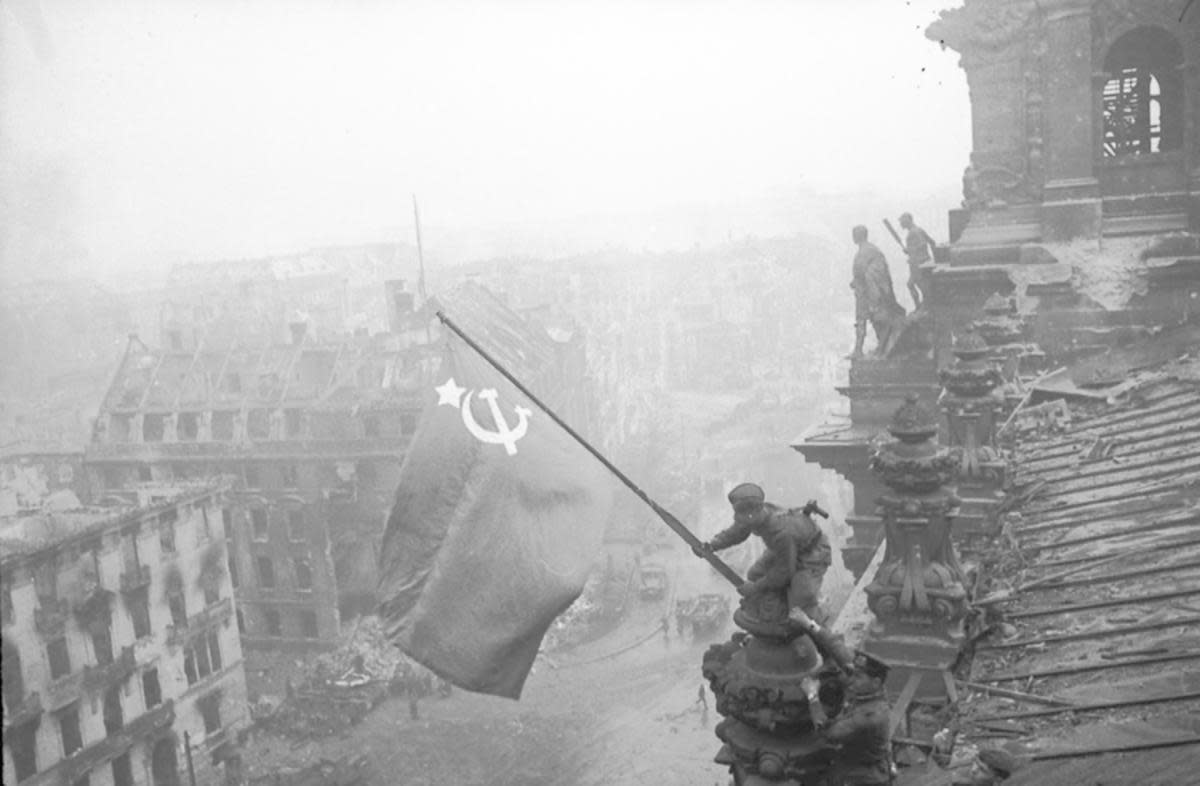 The famous photo of Soviet soldiers over Reichstag during the Battle of Berlin, which was later revealed to be staged and altered. (Credit: Sovfoto/UIG via Getty Images)