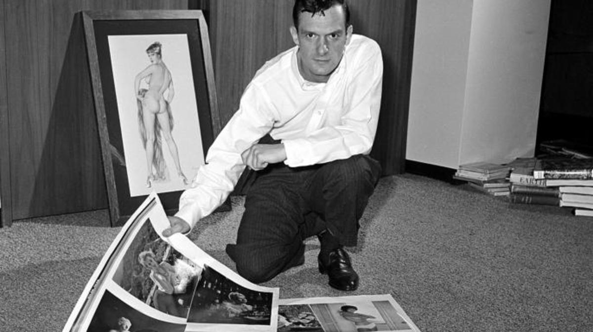 Publisher Hugh Hefner looking over proof sheets for his magazine Playboy, 1961.  (Credit: AP Photo)