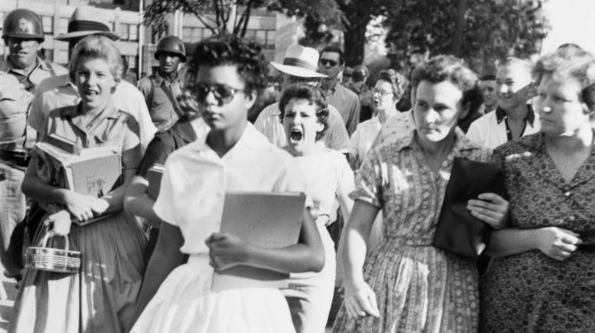 An alternate-angle view of Elizabeth Eckford on her first day of school, taken by an Associated Press photographer. Hazel Bryan can be seen behind her in the crowd. (Credit: Bettmann/Getty Images)