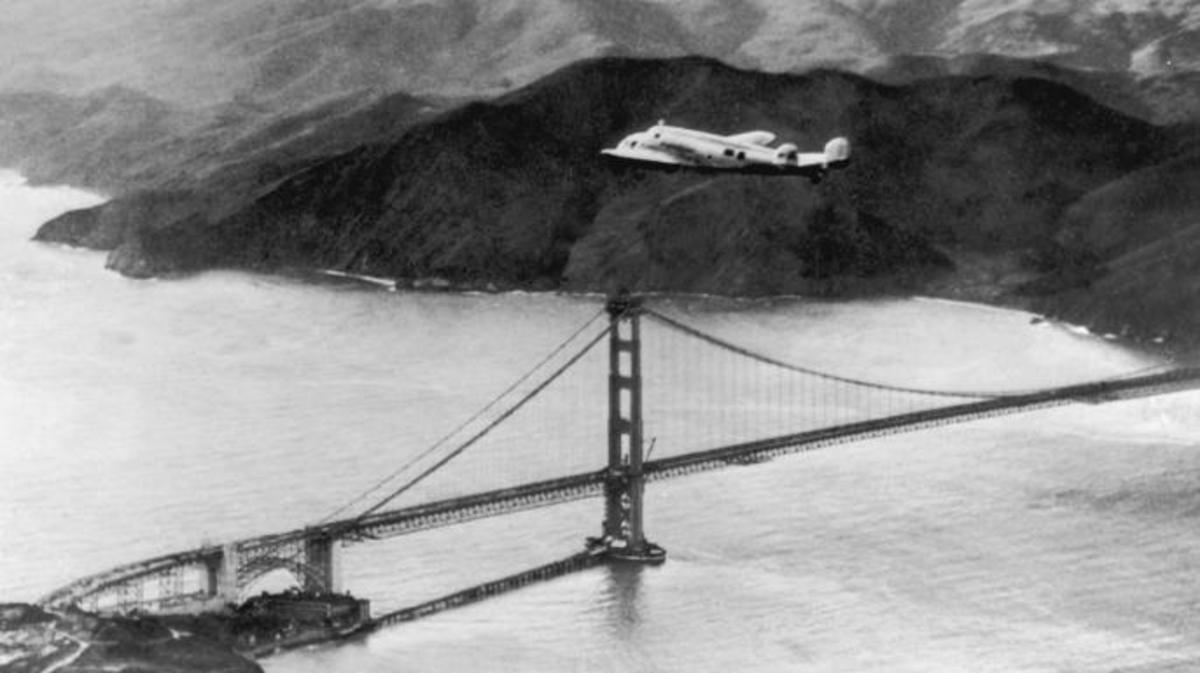 The Lockheed Electra 'Flying Laboratory', piloted by American aviator Amelia Earhart and Fred Noonan, over the Golden Gate bridge in California, at the start of a planned round-the-world flight. (Credit: Keystone/Hulton Archive/Getty Images)